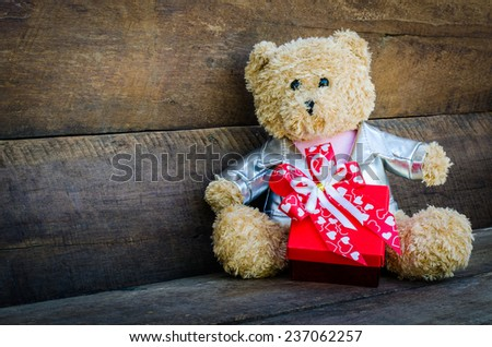 teddy bear and gift on wooden background
