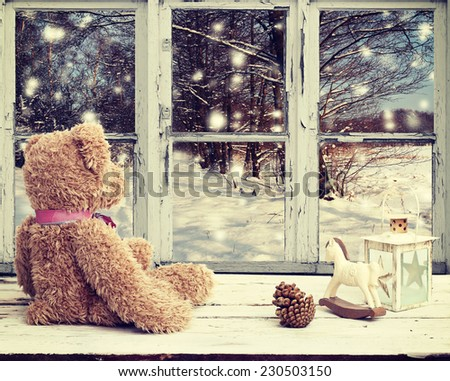 teddy bear and rocking horse looking at snowy night - stock photo