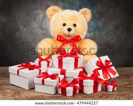 Teddy bear and white boxes with gifts on the old board.