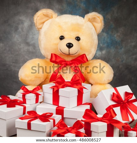 Teddy bear and white boxes with gifts on the old board. square version