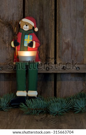 Teddy bear as santa claus with candle - stock photo