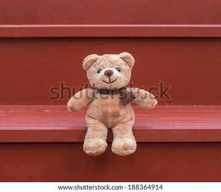 TEDDY BEAR brown color sitting on red staircase - stock photo