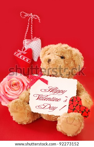 teddy bear holding a card with valentine`s greetings against red background