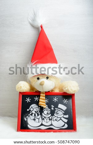 Teddy bear holding a painted artificial snow snowmen in red box