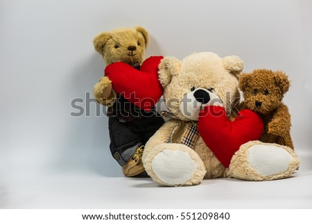 Teddy bear holding heart shape pillow on with background