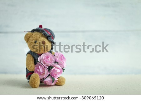 Teddy bear holding pink paper roses  - stock photo
