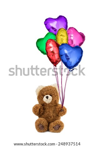 Teddy bear holds many helium gas filled colored heart balloons for saint valentine's day, birthday or other celebration. With pure white background to use as you wish. - stock photo
