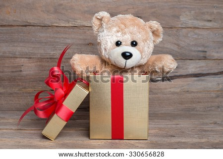 teddy bear in gift box on wooden background