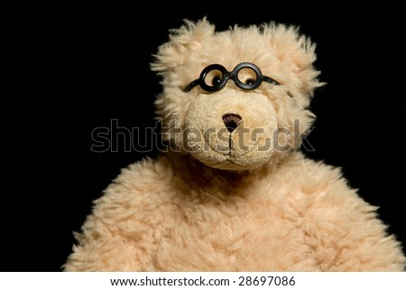 Teddy bear in glasses close up portrait on black background