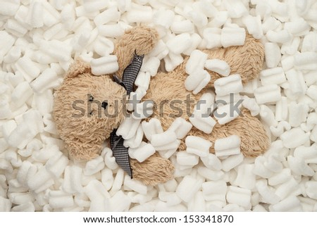 Teddy bear laying in a pile of packing peanuts