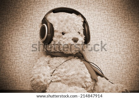 Teddy bear listening to music on headphones. Photo by sepia toned - stock photo
