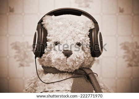 Teddy bear listening to music on headphones. Photo by sepia toned, retro style - stock photo