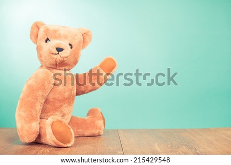 Teddy Bear old retro toy sitting front mint green gradient background - stock photo