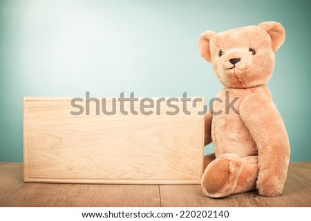 Teddy Bear old retro toy with signboard blank front gradient background - stock photo