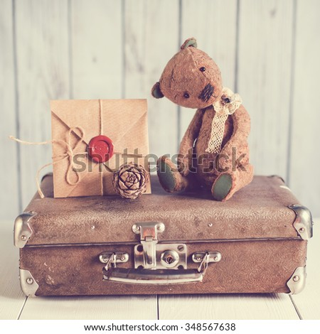 Teddy bear on a suitcase with a love letter - stock photo