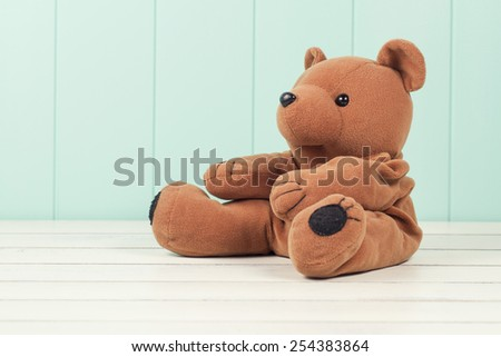 Teddy bear on a white wooden table with a robin egg blue wainscot. Vintage Style. - stock photo
