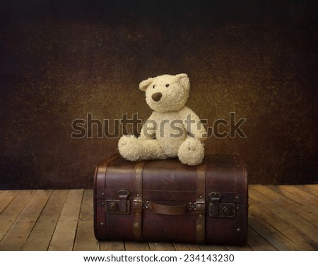 teddy bear on an old vintage suitcase, dark background - stock photo