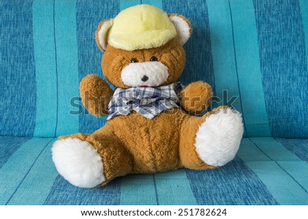 Teddy bear on blue bed - stock photo