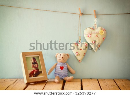 teddy bear over wood table next to photo frame with kid's old photography and fabric hearts. retro filtered image
