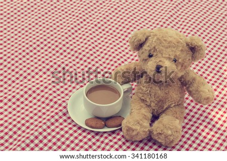 teddy bear picnic in the park sit on red and white fabric. have a cookie, coffee one cup and milk. vintage style. - stock photo