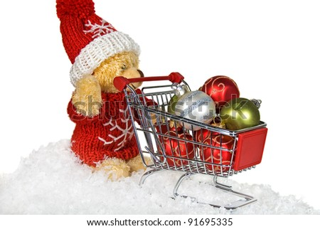 teddy bear pushing a shopping cart filled with ornaments - stock photo
