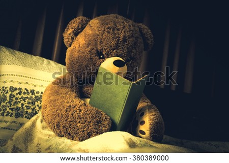Teddy bear read the book in bed, effect by vintage style - stock photo