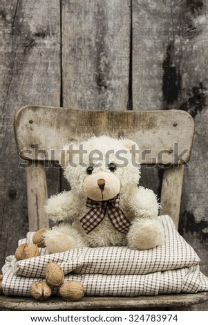 Teddy bear siting on chair with walnut