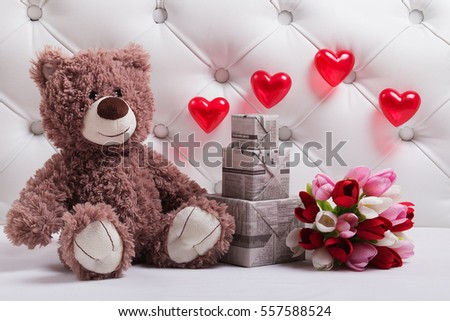 Teddy bear sits near the bouquet of tulip and three gift boxes. Toy, hearts and flowers. Background for a Valentines day postcard.