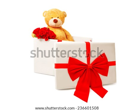 Teddy bear sitting in a gift box and  holding bouquet of red roses, valentines day. Studio shot, over white background with copy space.