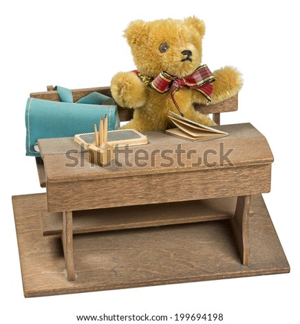 teddy bear sitting on a wooden pupils desk with his school satchel beside him. Isolated on white.  - stock photo