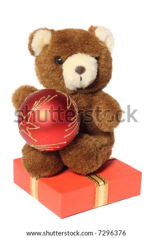 Teddy bear sitting on gift box with Christmas ball in hands, isolated on white background