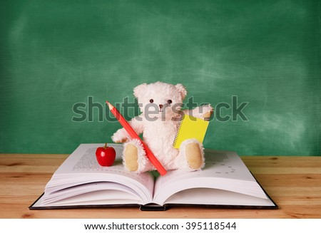 Teddy bear sitting on the opened book. in front of the black board. Kids library, education and school image.  - stock photo