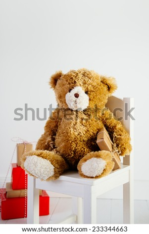 Teddy bear sitting on white wooden chair