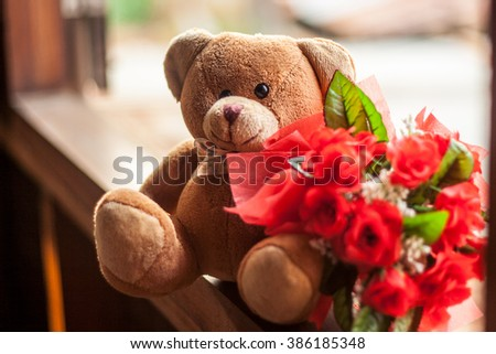 Teddy bear sitting on window with beautiful red roses bouquet. - stock photo
