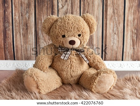 Teddy bear sitting on wooden background - stock photo