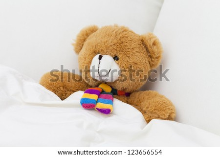 Teddy bear sleeping in a bed