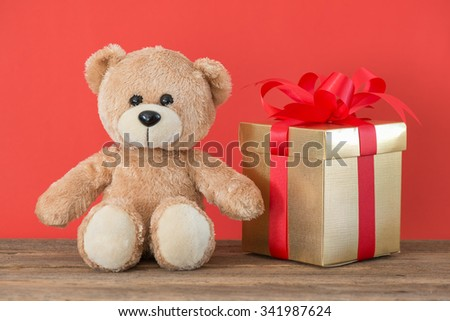 Teddy Bear toy alone and gift box on wood  with red background