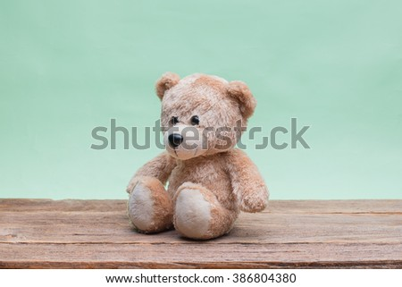 Teddy Bear toy alone on wood with light green background. - stock photo