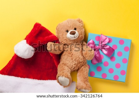 Teddy bear toy and gift with hat on yellow background