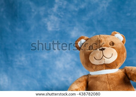 Teddy Bear toy on blue sky background with copyspace - stock photo