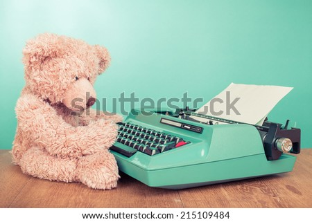 Teddy Bear toy with retro mint green retro typewriter on table concept - stock photo