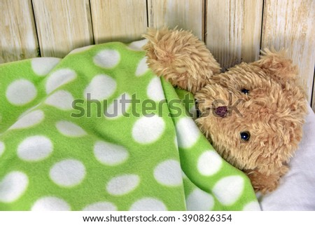 teddy bear under a green and white polka dot fleece blanket