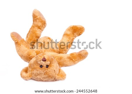 Teddy bear upside down, falling over. Isolated on white. - stock photo