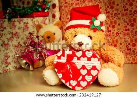 Teddy bear wearing a santa hat and gift.