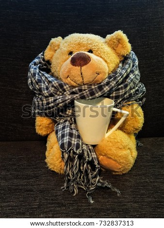 Teddy bear wearing checkered scarf siting stock photo 732837313 teddy bear wearing an checkered scarf siting on a couch with a cup of tea altavistaventures Choice Image
