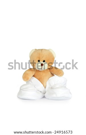 Teddy bear wearing baby booties over white background. - stock photo