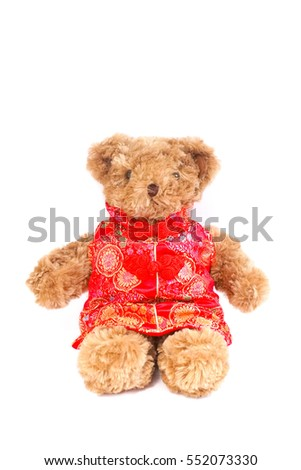 Teddy bear wearing Chinese traditional dress called Qipao. Teddy bear isolated on white background. Chinese character translated as wealth and happiness. Concept of lunar Chinese new year