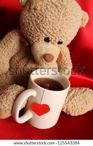 Teddy bear with a big white cup of tea and a red heart - stock photo