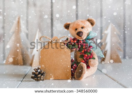 Teddy Bear with a blank for congratulations on a wooden background