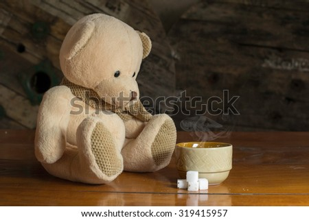 Teddy bear with a cup of coffee on a wood table.